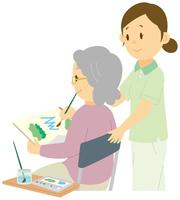 水彩画を描く老人女性と介護士