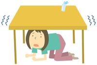 地震で机の下に避難する人