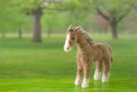 フェルトの馬と牧場の背景の合成