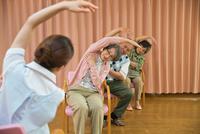 体操をするシニアと介護福祉士
