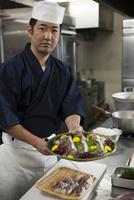 鯛の松皮造りの皿を差し出す調理師