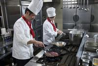 ステーキをフライパンで焼く調理師
