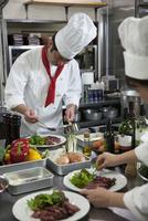 ステーキを皿に盛り付ける調理師