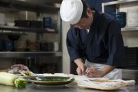 鯛の松皮造りを切る調理師