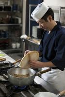 落し蓋と玉杓子を持つ調理師