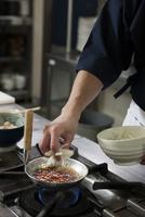 玉ねぎの薄切りを親子鍋で煮る調理師
