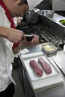 ステーキ用の肉に胡椒を振る調理師