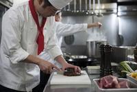 焼けたステーキを包丁で切る調理師