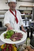 ステーキの皿を差し出す調理師