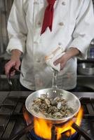 アサリをフライパンで調理する調理師