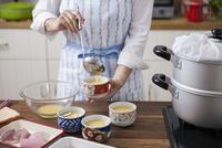 卵液を茶碗蒸しの容器に注ぎ入れる女性
