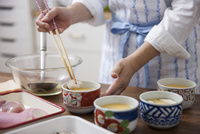 茶碗蒸しの具材を卵液に入れる女性
