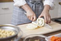 レンコンを包丁で切る女性