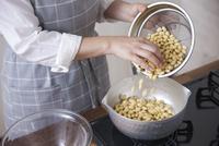 鍋に水で戻した大豆を入れる女性