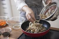 フライパンでささがきゴボウを炒める女性
