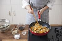 フライパンでゴボウとニンジンを炒める女性
