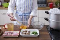 卵液を菜箸でほぐす女性