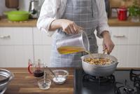 大豆と野菜を入れた鍋にだしを注ぐ女性