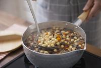 鍋で煮ている五目豆をお玉で掬う女性