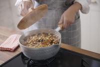 五目豆を煮ている鍋に落し蓋をする女性