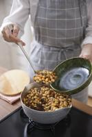 五目豆をお玉で掬って器によそう女性
