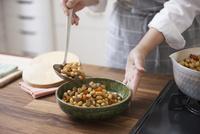 五目豆をお玉で器に盛り付ける女性