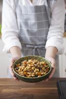 五目豆を入れた器を持つ女性