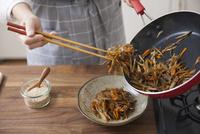 きんぴらごぼうを菜箸で器に盛り付ける女性