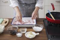 豚薄切り肉に小麦粉をまぶす女性