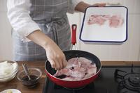 豚薄切り肉をフライパンに入れる女性