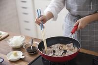 豚薄切り肉をフライパンで焼く女性