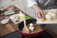 炒めた挽肉の中に豆腐を入れる女性