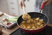 挽肉と豆腐と調味料を炒め合わせる女性