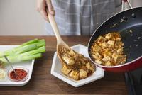 麻婆豆腐を器に盛り付ける女性