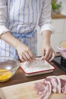 豚ロース肉に小麦粉をまぶす女性