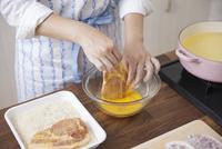 豚ロース肉に卵液をつける女性