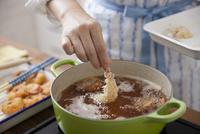 エビフライを油で揚げる女性