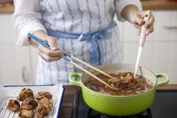 唐揚げを油で揚げる女性