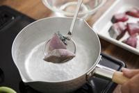 ブリの切身を熱湯に浸して霜降りにする女性