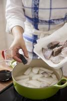 大根とブリの切身を鍋に入れる女性