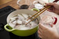 大根とブリの切身を鍋で煮る女性