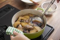 大根とブリを煮て醤油を加える女性