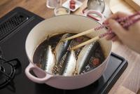 梅干しと煮汁でイワシを煮る女性
