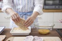 豚ロース肉にパン粉をつける女性
