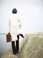 防波堤に立つトランクを持った日本人男性