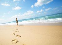 砂浜の足跡と日本人女性