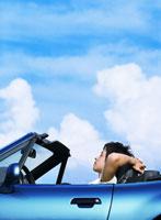 車に乗る日本人男性と青空