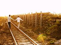 線路を歩くカップル