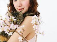 花とネコを抱いた女性