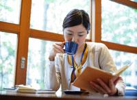 カップを持ち読書をする女性